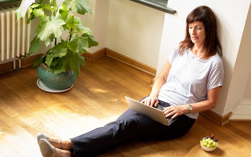 Vera Pieper auf Boden sitzend mit Laptop arbeitend. Fotograf: Guido Alfs