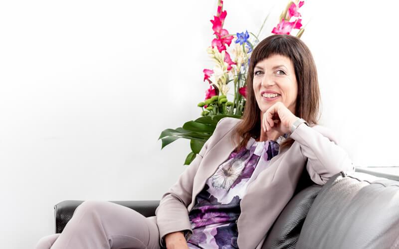 Porträt von Vera Pieper auf Sofa sitzend, mit Kinn auf Hand gelehnt. Fotograf: Guido Alfs