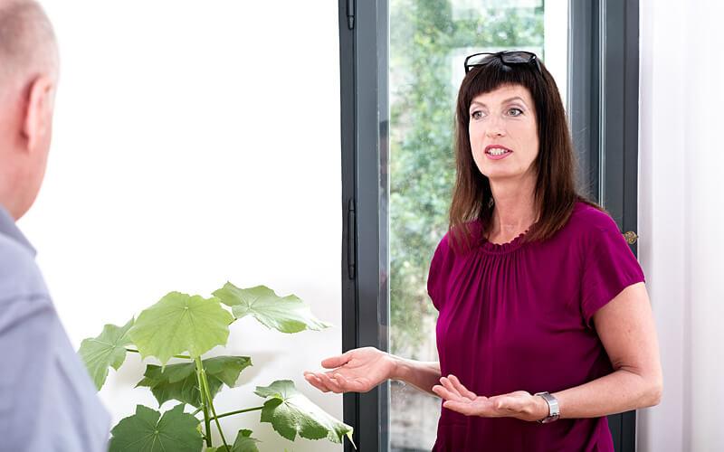 Vera Pieper im Gespräch mit Klienten, gestikulierend. Fotograf: Guido Alfs